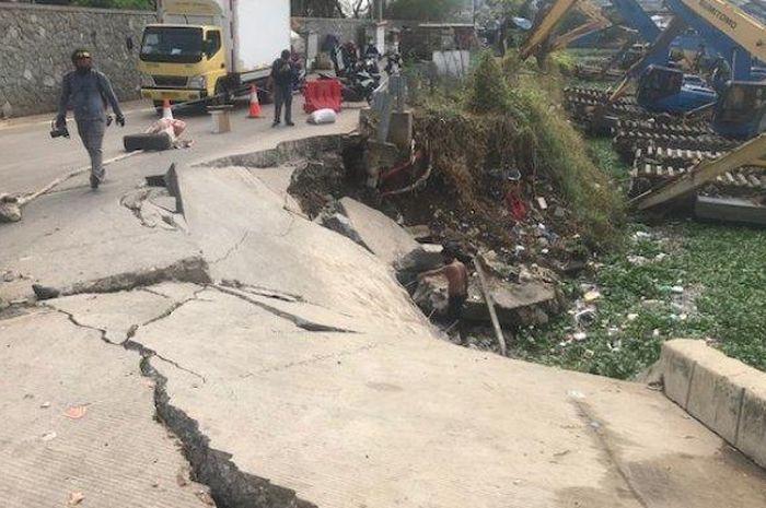 Jalan Raya Inspeksi Waduk Pluit, Penjaringan, Jakarta Utara amblas akibat tanah longsor membuat pemotor khawatir tertimpa musibah saat melintas.