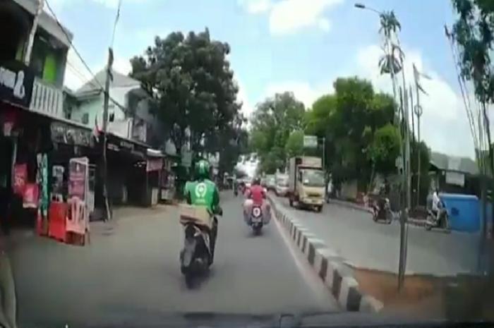 Bahaya, driver ojol naik motor sambil main HP sampai oleng, udah diklaksonin malah pura-pura budek.