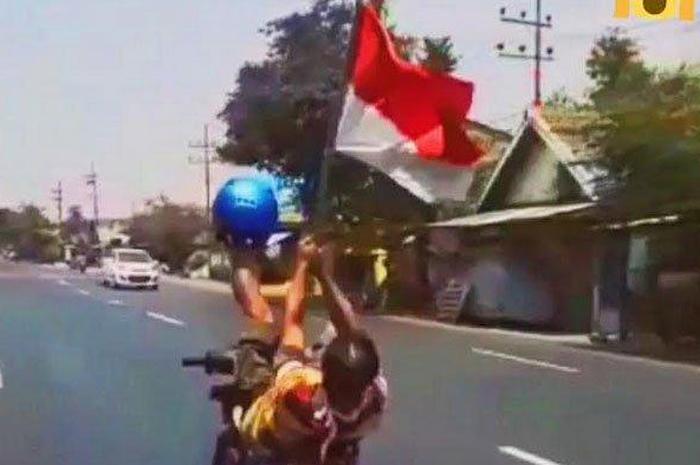 Viral Aksi Pemotor yang Tiduran di Atas Motor Sambil Bawa Bendera, Polisi Langsung Bilang Begini