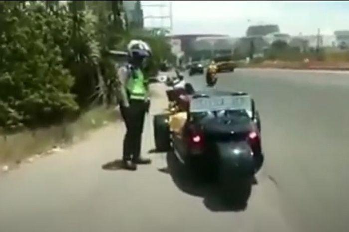 Sebuah video viral setelah merekam detik-detik polisi menilang motor mewah roda tiga milik Bupati Karawang, Cellica Nurrachadiana.