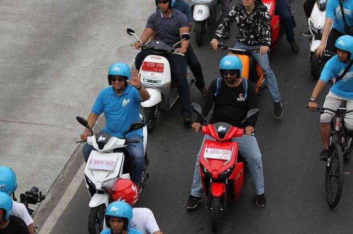 Gubernur DKI Jakarta Anies Baswedan melambaikan tangan saat konvoi menggunakan kendaraan listrik  di Festival Langit Biru, Bundaran Senayan, Jakarta Pusat, Minggu (27/10/2019). Kampanye tersebut bertujuan mengenalkan kendaraan listrik yang ramah lingkungan guna mengurangi polusi udara.