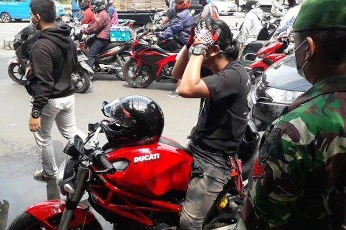 Seorang pengendara motor disetop oleh anggota TNI karena tidak mengenakan masker saat berkendara di Simpang CCM, Kabupaten Bogor, Selasa (15/9/2020)