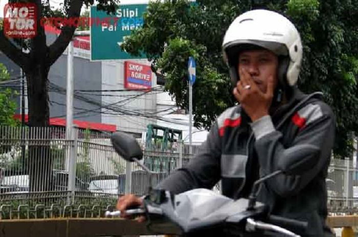 Ilustrasi naik motor sambil merokok.