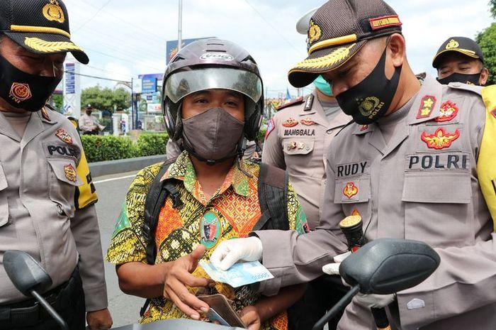 Kapolres Kebumen AKBP Rudy Cahya Kurniawan memberikan hadiah uang kepada pengendara yang patuh menggunakan masker saat operasi yustisi di sekitar Alun-alun Kebumen, Jawa Tengah, Rabu (30/9/2020).
