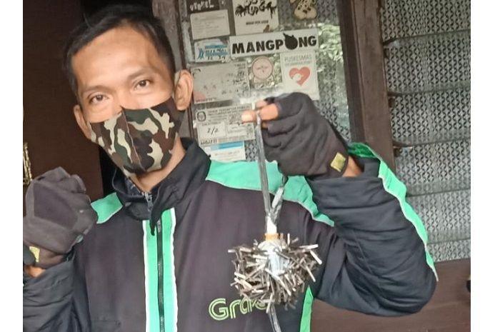 Uum Hidayat, driver ojol penyapu ranjau paku di jalanan Jakarta.