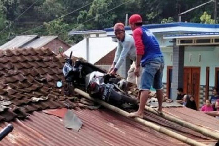 Motor matic nyangkut di atap rumah warga