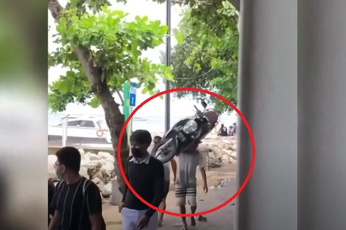 Geger, seorang pria sekuat samson, menggendong motor Honda Scoopy dengan santainya di pinggir dermaga.