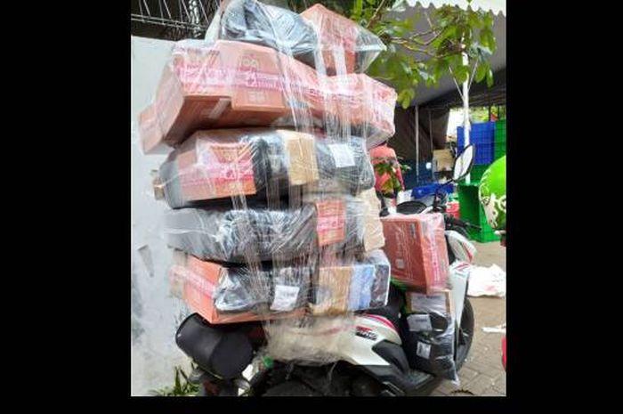 Ilustrasi kurir Shopee bawa barang bertumpuk-tumpuk. Para kurir Shopee di wilayah Bandung Raya melakukan mogok kerja karena upah murah.