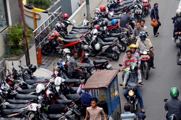 Ilustrasi motor parkir sembarangan sehingga membuat sebagian jalan tertutup.