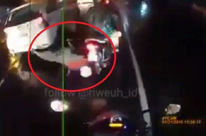 Seorang pembonceng motor terjungkal karena jas hujan masuk ke gir motor.